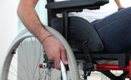 Closeup of a man's hand on the wheel of his wheelchair